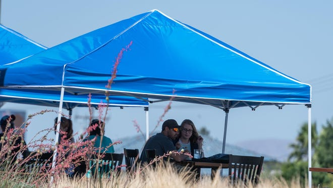 Diners eat under canopies in front of BJs Restaurant & Brewhouse in Victorville on July 4, 2020.