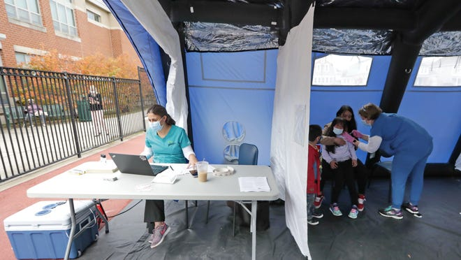A mom offers her daughter as much comfort as possible as RN Jessica Prince administers a flu vaccine inside the tent  set up outside of the Abraham Lincoln Elementary School on Ashley Boulevard in New Bedford to offer teachers, students and their families flu vaccines.