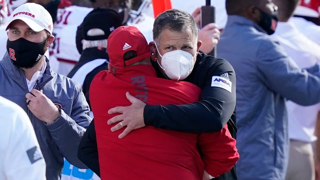 Rutgers coach Greg Schiano, with a mask, is hugged by an assistant after his team defeated Michigan State in East Lansing.