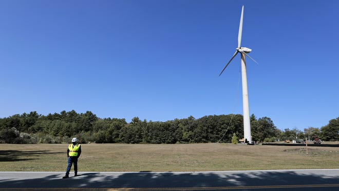 The wind turbine at UMass Dartmouth is seen in the background shortly before it was toppled over for removal.