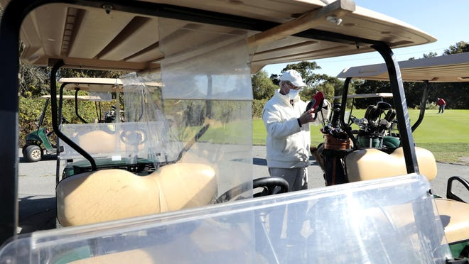 Golf carst with transparent plastic barriers between driver and passenger can be seen in the foreground as Brian Ott prepares his golf clubs on the back of the golf cart he has been assigned. at the Whaling City Golf Course.