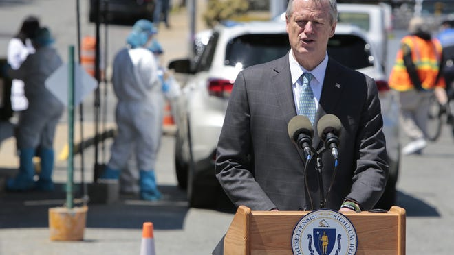 Massachusetts governor Charlie Baker addresses the media as in the background Stanley Street Treatment and Resources technicians can be seen performing COVID-19 testing at South Main Street testing station in Fall River.