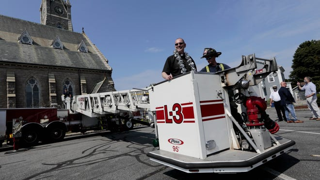 Fr Mike Racine is taken on a ride in one of the fire engine truck lifts during the 25th anniversary of his ordination, held in the parking lot of the Saint Lawrence church in New Bedford. Fr Racine is the chaplain of both the Fall River and New Bedford fire departments.