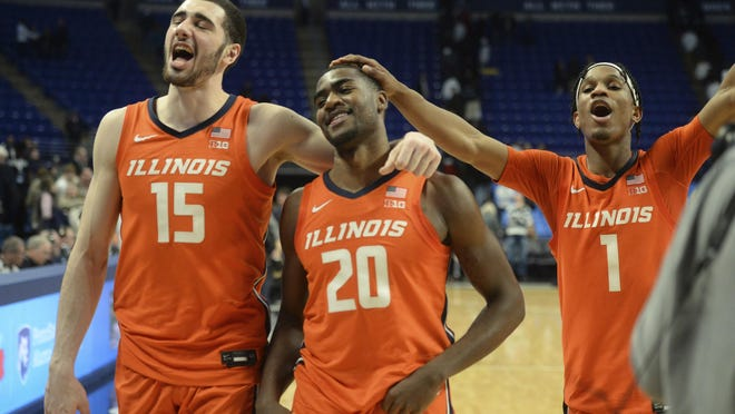 Illinois' Giorgi Bezhanishvili (15), Da'Monte Williams (20) and Trent Frazier (1) leave the court after Illinois defeated Penn State 62-56 in an NCAA college basketball game Tuesday, Feb. 18, 2020, in State College, Pa.