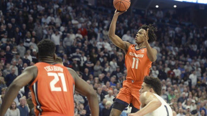 Illinois' Ayo Dosunmu's (11) scores against Penn State in the final minute on Feb. 18, 2020 in State College, Pa Watching the shot are Illinois' Kofi Cockburn (21) and Penn State's Seth Lundy (1).