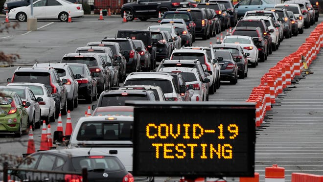 Hundreds of motorists line up at the Whale's Tooth parking lot in New Bedford, Mass., to be tested for the coronavirus.