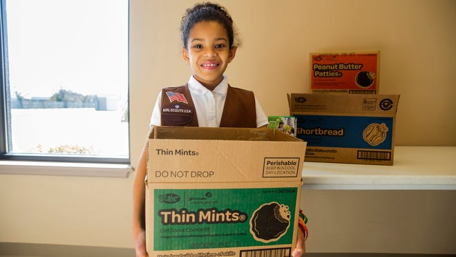A Girl Scout with her delivery box of your favorite fundraising cookie effort.