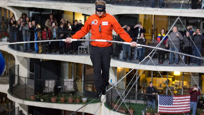 This photo provided by Discovery Communication shows Nik Wallenda walking across the Chicago skyline blindfolded for Discovery Channel's Skyscraper Live with Nik Wallenda on Nov. 2.