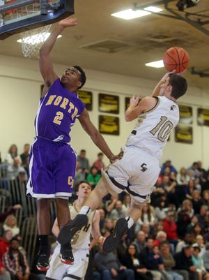 Clarkstown South's Andrew Bunyan shoots over Clarkstown North's J.R. Levy during a varsity basketball game Friday at Clarkstown South High School in West Nyack. Clarkstown South won 56-43.