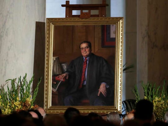 FILE - In this Friday, Nov. 4, 2016 file photo, a portrait of the late Supreme Court Justice Antonin Scalia is displayed during a memorial for him held in the Great Hall of the Supreme Court building in Washington. After Scalia's death in February 2016, President Barack Obama nominated Merrick Garland, chief judge of the U.S. Court of Appeals, to fill the vacancy. However, majority Republicans in the Senate refused to consider the nomination, opting to leave the seat vacant so it could be filled by the winner of the presidential election. Donald Trump has promised to appoint a conservative in the mold of Scalia.