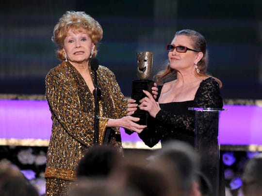 "FILE- In this Jan. 25, 2015, file photo, Carrie Fisher, right, presents her mother Debbie Reynolds with the Screen Actors Guild life achievement award at the 21st annual Screen Actors Guild Awards at the Shrine Auditorium in Los Angeles. ""La La Land"" star Ryan Gosling thanked Reynolds at the Palm Springs Film Festival on Monday, Jan. 2, 2017, for serving as an inspiration to the cast and crew of the film."