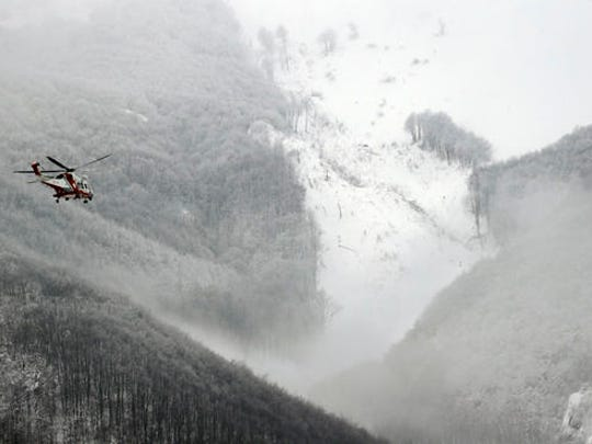 A rescue helicopter flies towards the area hit by an avalanche, seen on the mountain's crest in the background, which buried a hotel, near Farindola, central Italy, Friday, Jan. 20, 2017. Rescue crews located up to eight people alive in the kitchen of an avalanche-crushed hotel on Friday, an incredible discovery that boosted spirits two days after the massive snow slide buried around 30 people in the resort.