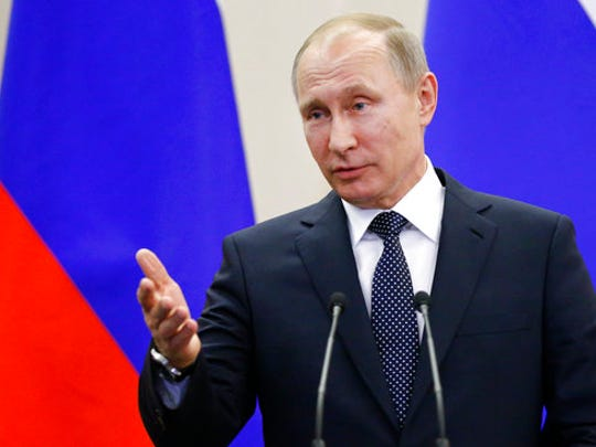 Russian President Vladimir Putin gestures as he speaks