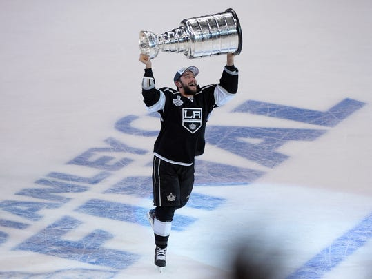 Los Angeles Kings defenseman Alec Martinez carries the Stanley Cup after beating the New York Rangers in Game 5 of the NHL Stanley Cup Final series Friday, June 13, 2014, in Los Angeles. The Kings won, 3-2, with Martinez scoring the winning goal in double overtime. (AP Photo/Mark J. Terrill)