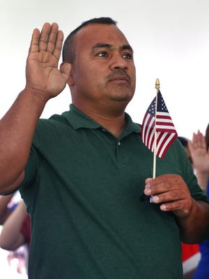 Jesus Tafoya, 41, who came from Mexico 23 years ago, holds an American flag as he and 96 others became American citizens during a naturalization ceremony July 2. This week, 100 people will become citizens during a ceremony at the Indiana War Memorial.
