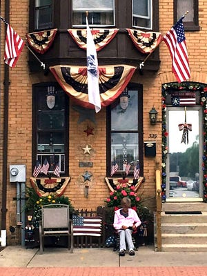 Rae Ann O'Connor sits outside and reads a book in front of her patriotically decorated home in late August.