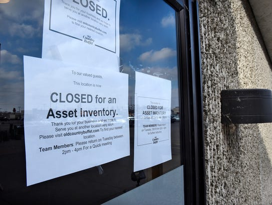 Signs announce the closing of Old Country Buffet on
