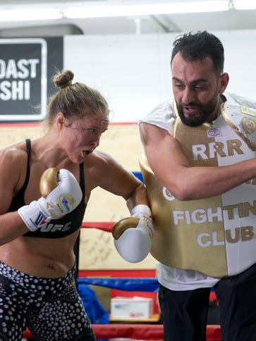 Mixed martial arts fighter Ronda Rousey, left, trains