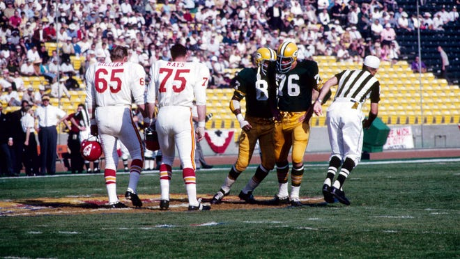 Green Bay Packers captains Willie Davis (87) and Bob Skoronski (76) meet Kansas City Chiefs captains for the coin toss before the start of Super Bowl I at The Coliseum in Los Angeles.