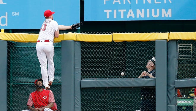 Cincinnati Reds right fielder Scott Schebler (43) climbs the fence as a fly ball off the bat of St. Louis Cardinals first baseman Jose Martinez (38) lands in the bullpen during the top of the first inning of the MLB National League baseball game between the Cincinnati Reds and the St. Louis Cardinals at Great American Ball Park in downtown Cincinnati on Friday, June 8, 2018. The Reds trailed 2-1 after two innings.