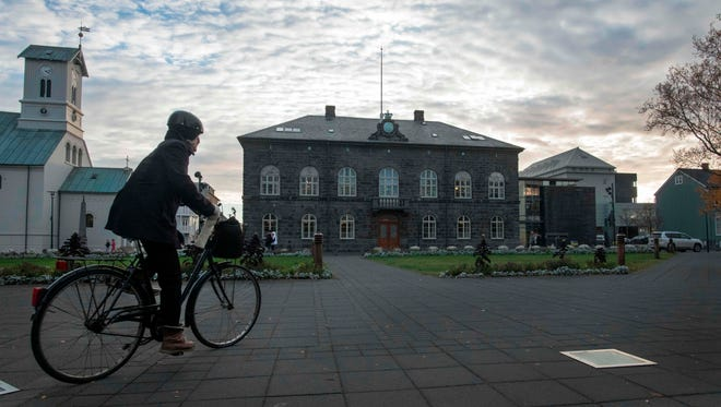 A woman bicycles past the Althingi Parliament building in Reykjavik, Iceland, on Oct. 24, 2017.  I