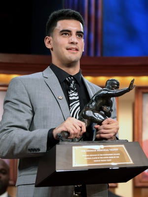 In this photo provided by the Heisman Trust, Oregon quarterback Marcus Mariota holds the Heisman Trophy after being named college football's best player during the Saturday's presentation in New York.