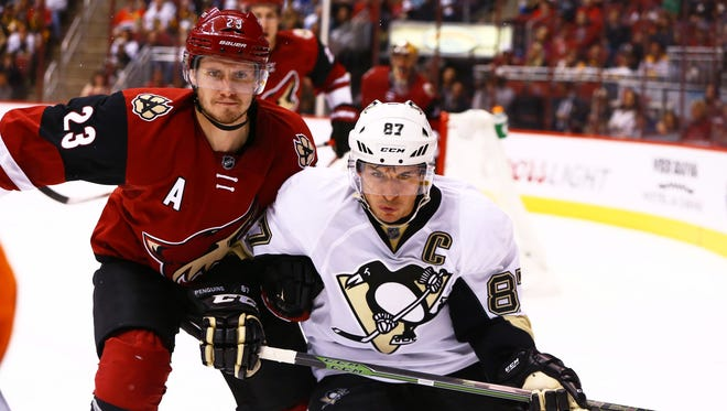 Oct. 10, 2015; Glendale; Pittsburgh Penguins center Sidney Crosby (right) and Arizona Coyotes defenseman Oliver Ekman-Larsson battle for the puck in the third period during the Coyotes' home opener at Gila River Arena.