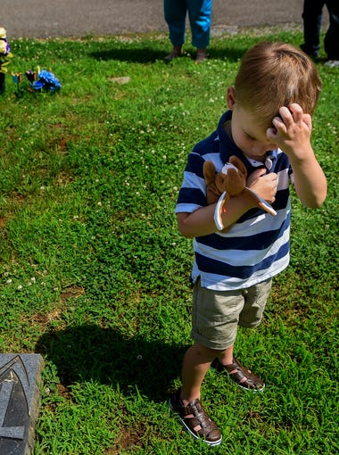 Four-year-old Tyler Hardin holds a toy that once belonged to his mother, Heather, as he visits her grave with his sister and grandparents at Calvary Cemetery in Nashville on Sunday, May 27, 2018.