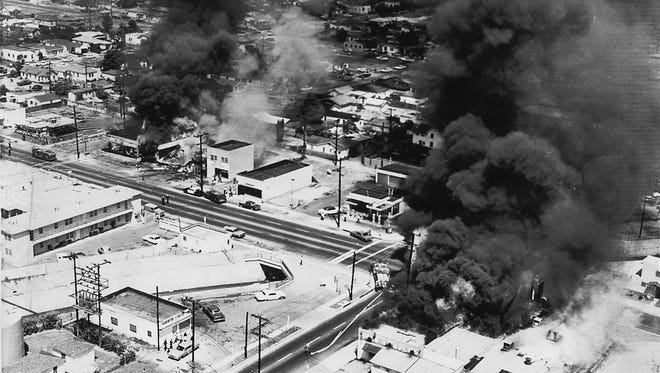 Buildings are shown on fire amid rioting in the Watts neighborhood of Los Angeles in August 1995.