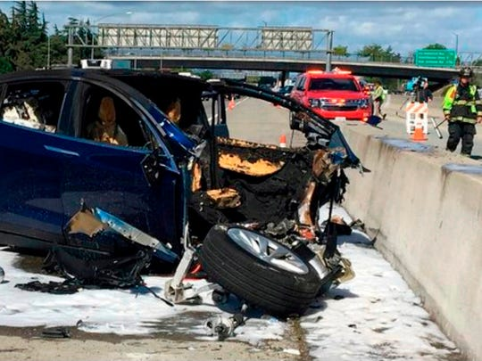In this March 23, 2018, file photo provided by KTVU, emergency personnel work at the scene where a Tesla electric SUV crashed into a barrier on U.S. Highway 101 in Mountain View, Calif. Federal safety investigators have booted electric car maker Tesla Inc. from the group investigating a fatal crash in California that involved an SUV operating with the company's Autopilot system. The National Transportation Safety Board said Thursday, April 12, it removed Tesla as a party to the investigation after the company prematurely made information public. (KTVU via AP, File)