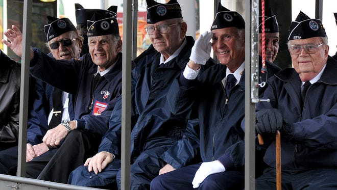 Korean war veterans wave and salute to parade-goers at a past Veterans Day parade in downtown Mansfield.