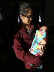 Stacy Hang, 21, cradles her newborn daughter Vienna
