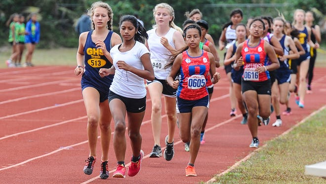 Runners compete in the girls' 3,000-meter race during the Independent Interscholastic Athletic Association of Guam track event at Okkodo High School in Dededo on April 8.