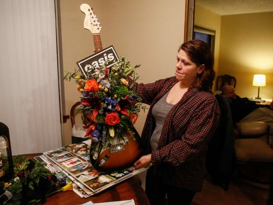 Amber Hayes holds up a guitar belonging to her son,