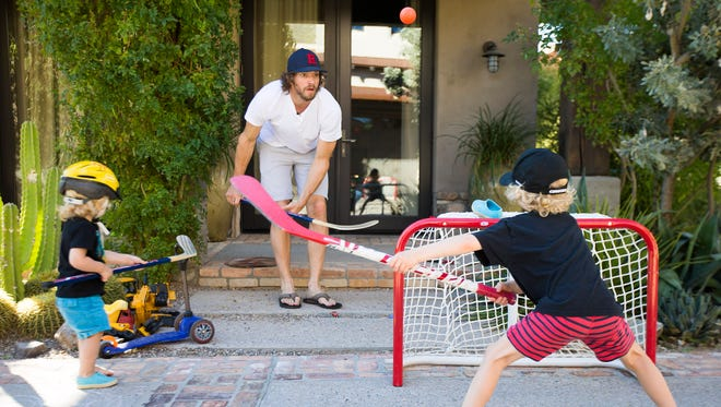 Arizona Coyotes goalie Mike Smith plays hockey with Nixon (left), 1, and Aksel, 4, on the driveway of their Scottsdale home February 17, 2016. Smith has been out since December with a core muscle injury.