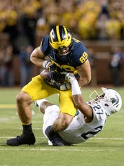 Michigan State's Khari Willis, right, tackles Michigan's Ian Bunting during the first quarter on Saturday, Oct. 7, 2017, at Michigan Stadium in Ann Arbor.