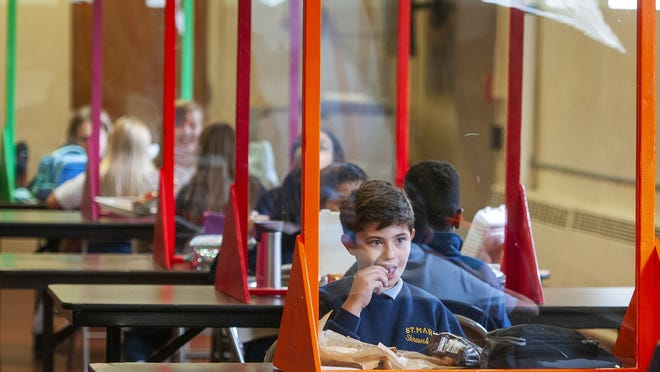 Anthony Silva, 5, eats lunch behind a clear barrier in the cafeteria Friday at St. Mary School in Shrewsbury.