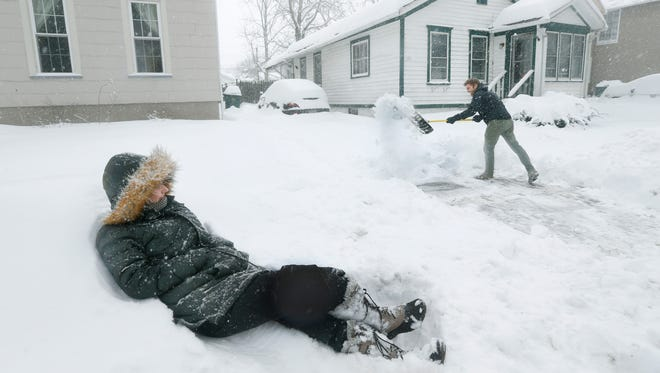 Jennifer Wick lays on the snow as her boyfriend Chris Noel shovels the driveway on Averill Street during a snowstorm on Tuesday.