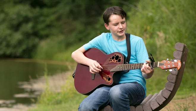 David Berry plays on his guitar at Brookside West Park in Ashland. Berry loves to play songs by country music icons such as Johnny Cash and Waylon Jennings, and he performed with Bobby Mackey.