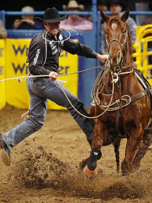 Trevor Brazile competes in the tie-down roping event for a first place time of 6.5 seconds during the eighth go-round of the National Finals Rodeo Thursday in Las Vegas. The time tied the arena record for the event.