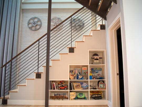 A shelf of toys sits underneath the second-floor staircase.