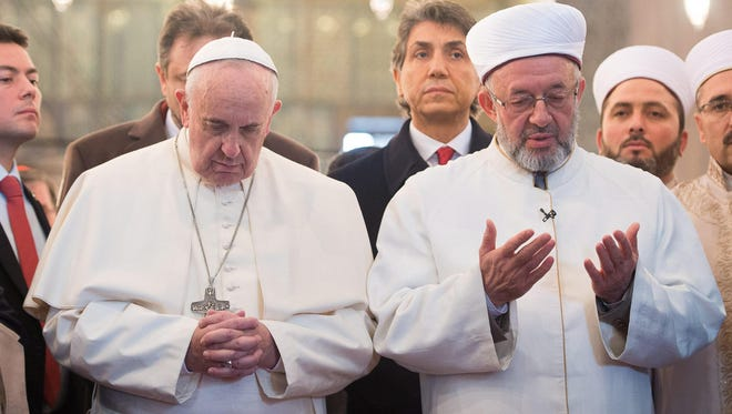Pope Francis prays with Mufti Rahmi Yaran, right, after their arrival in the Sultan Ahmed Mosque in Istanbul on Nov. 29, 2014.