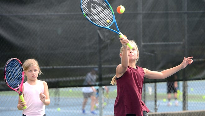 Annie Ward, 10, hits as Emory Cross, 8, waits her turn on Tuesday, August 11, 2020 at Creekmore Tennis Center in Fort Smith. The girls along with others were participating in the center's youth tennis clinic instructed by Southside senior tennis player Annie Nelligan.