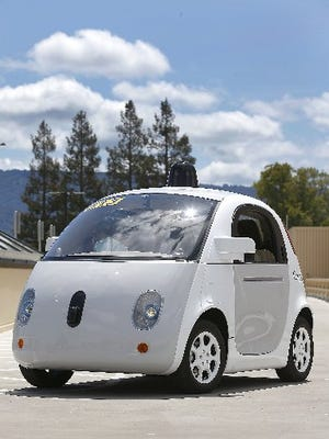 Google's new self-driving prototype car drives around a parking lot during a demonstration at Google campus in Mountain View, Calif. The car, which needs no gas pedal or steering wheel, will make its debut on public roads this summer.