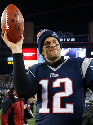 "FILE - In this Jan. 10, 2015, file photo, New England Patriots quarterback Tom Brady holds up the game ball after an NFL divisional playoff football game against the Baltimore Ravens in Foxborough, Mass. With the start of the new NFL season less that a month away, Patriots quarterback Brady will skip practice to attend a federal court hearing in Manhattan in the legal battle over whether he can take the field in next month's opener.  The NFL Players Union has sued to get a judge to void NFL Commissioner Roger Goodell's four-game suspension of Brady in the ""Deflategate"" scandal, setting the stage for the spectacle of the pair having to appear on Wednesday Aug. 12, in the same courtroom. (AP Photo/Elise Amendola, File)"