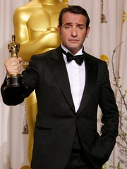 "FILE - This Feb. 26, 2012 file photo shows Jean Dujardin with his award for best actor for ""The Artist"" during the 84th Academy Awards in the Hollywood section of Los Angeles. Dujardin portrayed silent movie actor George Valentin at the arrival of talking pictures."