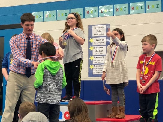 Second-graders receive medals at Riverside's Math Olympics.