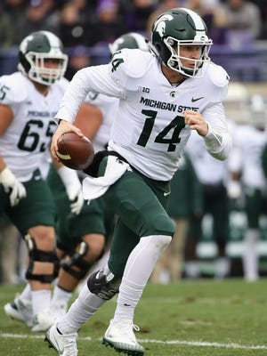 Brian Lewerke #14 of the Michigan State Spartans runs for a first down against the Northwestern Wildcats at Ryan Field on October 28, 2017 in Evanston, Illinois.