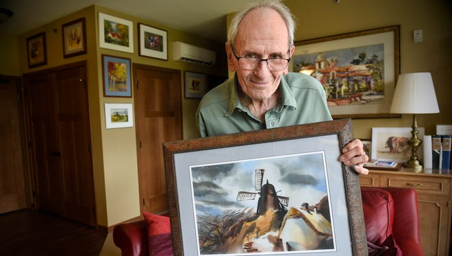"""Mick Benson holds his painting """"The Borglum Windmill"""" Friday, Aug. 25, at his home in Sartell. Benson's work won a gold medal in the Red River Watercolor Society's national exhibition."""