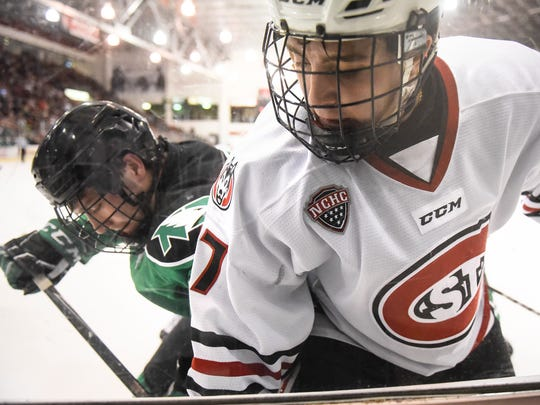 Colton Poolman of North Dakota and St. Cloud State's Jacob Benson work along the boards during the first period of the Saturday, Dec. 9, game at the Herb Brooks National Hockey Center in St. Cloud.